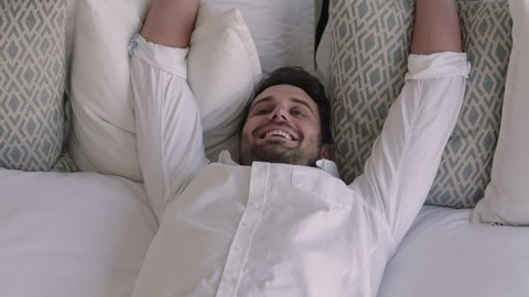 happy man jumping on bed resting after successful travel journey smiling enjoying independent lifestyle freedom