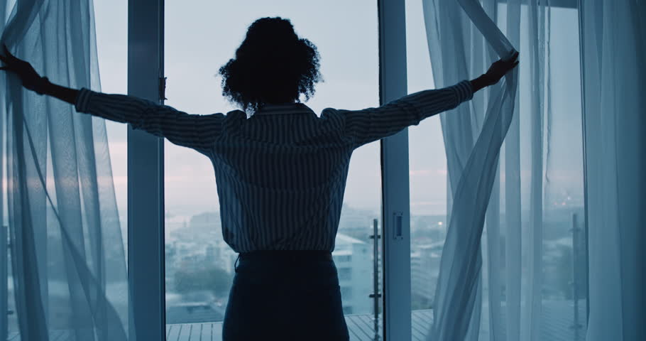 business woman opening curtains in hotel room looking out window at fresh new day successful independent female planning ahead on cloudy morning