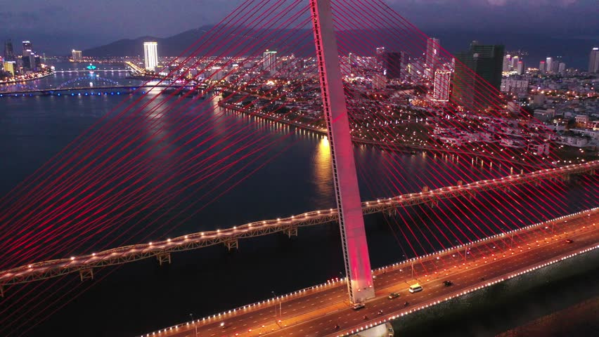 Aerial top view Tran Thi Ly Bridge, Han river in Da Nang City, Vietnam Da Nang city at sunset which is one of the most beautiful place of Vietnam for tourists. | Shutterstock HD Video #1024439120