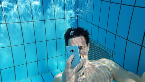 A man texting and taking photos with a phone under water in a swimming pool