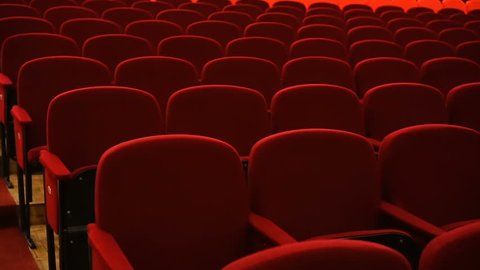 Rows of empty red velvet seats inside a theater or opera.