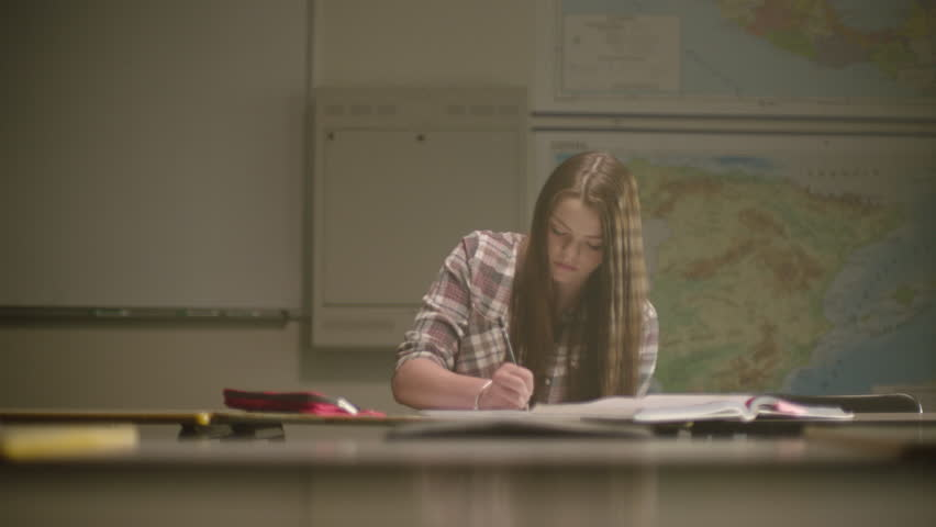 Female student in classroom surrounded by textbooks writes in her notebook working on school work in a classroom setting with map behind her. Filmed with Arri Alexa Mini | Shutterstock HD Video #1024494380