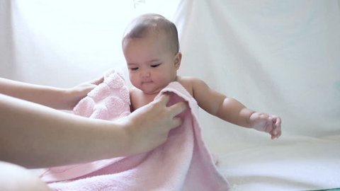 Mother wiping baby girl using pink towel, baby getting dry after shower