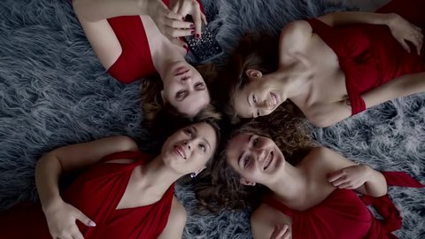 Group of a bridesmaids lying on the floor blowing a kiss. Four beautiful girls in lovely dresses, hen party shoot. Bachelorette event.
