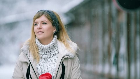 0f4e70a5e Happy young blonde woman drinks hot tea or coffee from a disposable red cup  on snowy
