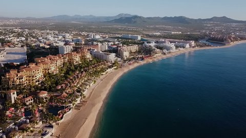 Aerial view of Medano Beach in Cabo San Lucas. Hotels at the front and the city behind. Shot at first hours in the morning. Baja California Sur, Mexico.