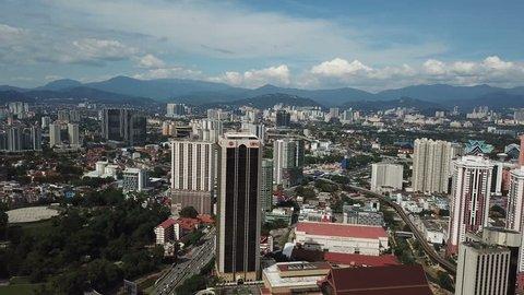 Kuala lumpur, malaysia - february 12, 2019: fly moving down at kuala lumpur  skyline near pwtc, sunway putra and hotel with bright sun and cloudy sky