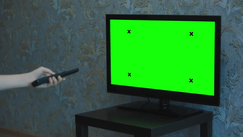 A Female hand switches channels on a TV with a green screen. TV stands on a small black table. Monitor in a room with blue wallpaper. | Shutterstock HD Video #1024603790