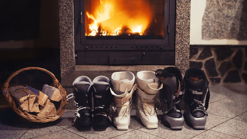 4k three pairs of skiing boots sit near glowing fireplace and basket of kindling. Winter holidays concept. #1024618700