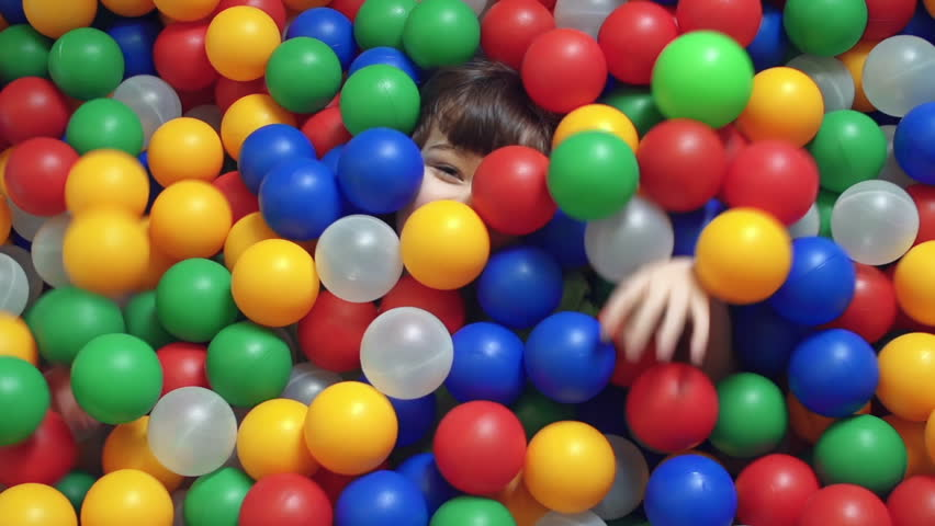 Direct from above view of little boy lying in the ball pit covered by multicolored hollow balls