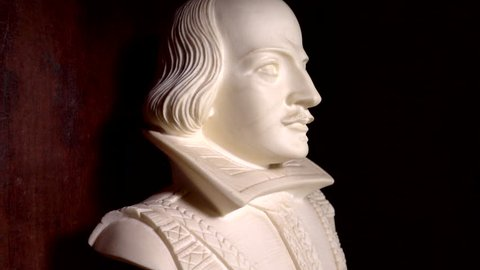 A slow motion close POV forward dolly shot of a Shakespeare bust on display in a wooden cabinet.