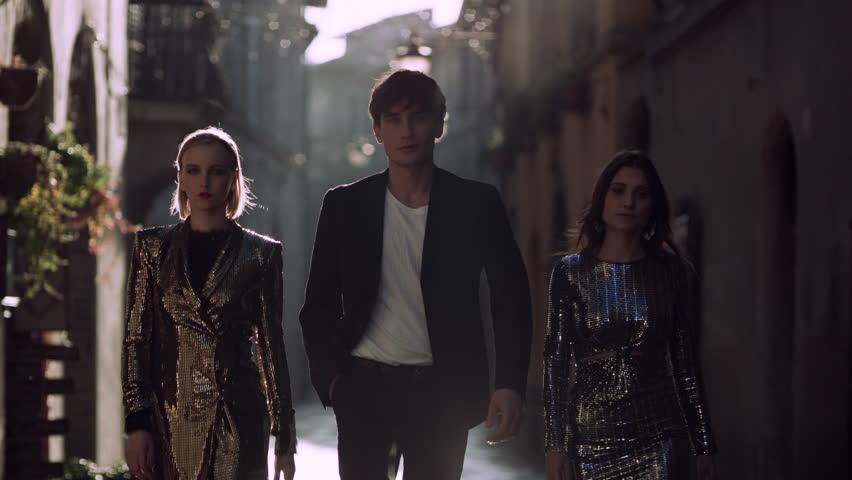 Group of fashionable Italian models walking together happily in stylish clothing through a quiet street in Bevagna, Italy, with bright sunset light. Medium shot on 8k helium RED camera.