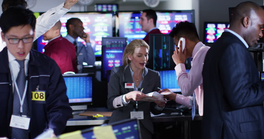 4K A busy room full of financial traders, watching the world markets and doing deals over the phone