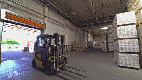 VINNITSA, UKRAINE - MAY 2018: Operator in a helmet drives a yellow electric forklift through the warehouse in search of the right product on the background of huge shelves.