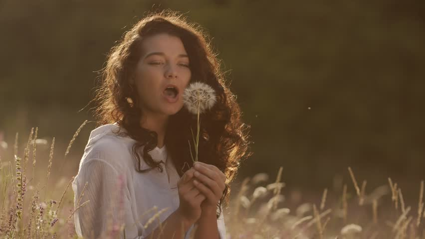 Beautiful Young Woman sitting on the field in green grass and blowing dandelion. Outdoors. Enjoy Nature. Healthy Smiling Girl on summer lawn. Allergy free concept. Gorgeous slim mixed race Caucasian