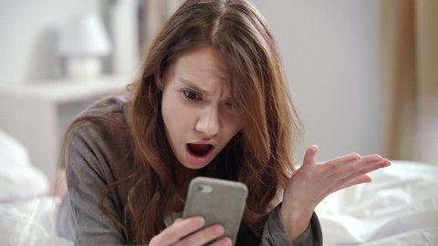 Shocked woman watching video news online on mobile phone at morning. Surprised woman face looking at smartphone in bedroom. Close up of young woman looking shocked video online on mobile phone