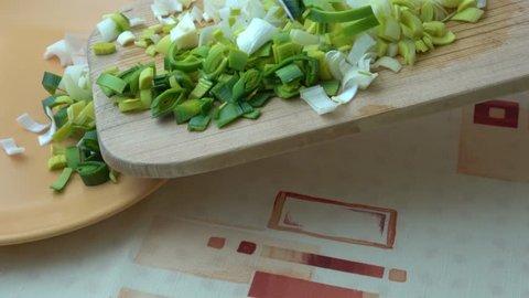 Natural fresh cutted leeks on the wooden cutting board. Closeup of sliced leek. Slices of the fresh green leek. Chopped Leek. Fresh vegetables.