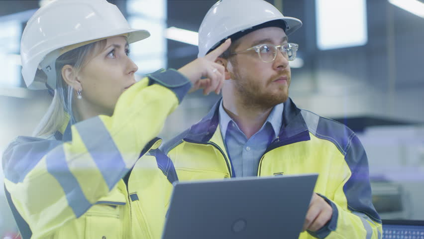 At the Factory: Male Mechanical Engineer Holds Component and Female Chief Engineer Work on Personal Computer, They Discuss Details of the 3D Engine Model Design for Robotic Arm.   Shutterstock HD Video #1024871570