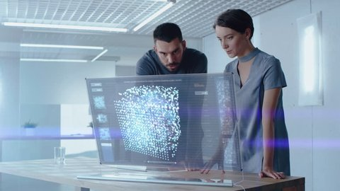 Futuristic Concept: Male and Female Computer Engineers Talk While Working on the Holographic Display Computer. Screen Shows Interactive Neural Network, Artificial Intelligence Project, User Interface