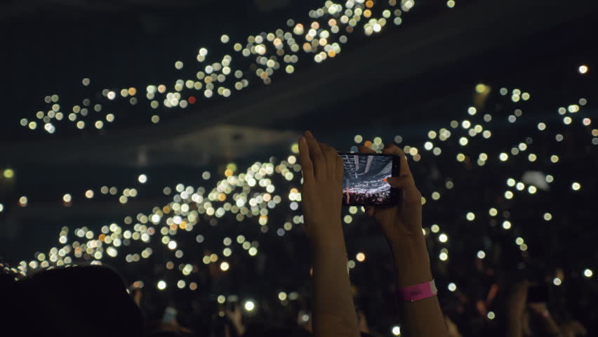 Woman taking mobile video of crowded concert hall. People with lights in the darkness | Shutterstock HD Video #1024883120