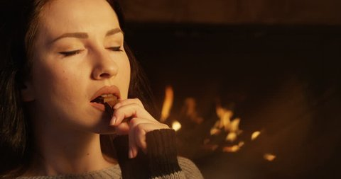 Portrait of Woman Indulging in Eating Chocolate Bar Feeling Intimate at Fireplace shot on Red Camera