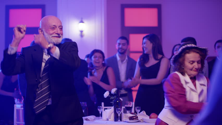 Stylish elderly couple having fun dancing at a colorful party . Sweet senior couple smiling and partying during party . Active retirement . Shot on RED HELIUM Cinema Camera in slow mo