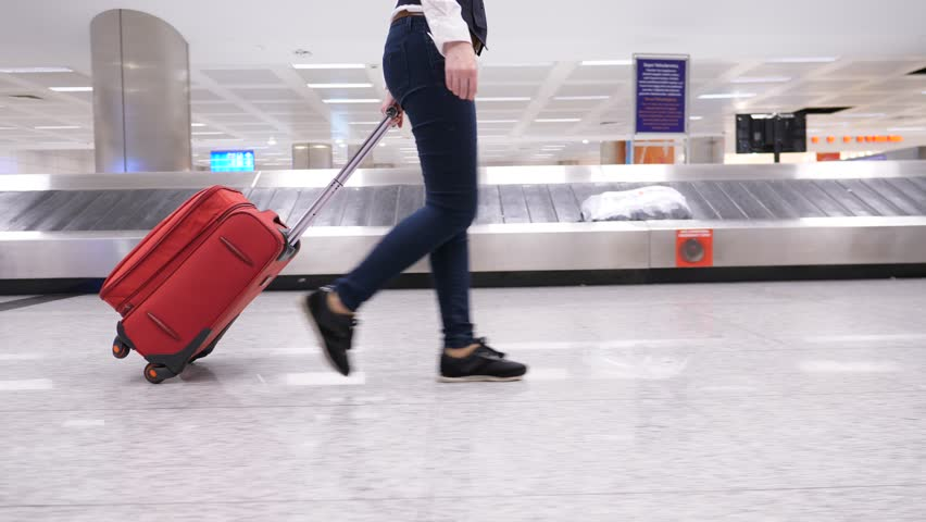 Woman hold trolley case handle and quickly walk to exit across luggage reclaim hall. Lower half tracking camera motion, side view of legs and wheeled suitcase, baggage carousel slide on background | Shutterstock HD Video #1024898960