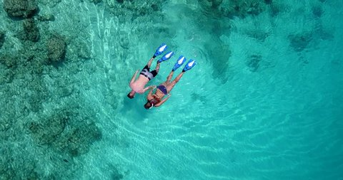 Aerial Circular traveling shot Young couple snorkelling and scuba diving in a Coral reef in Maldives Island