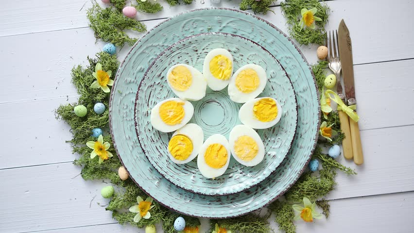 Easter table setting with flowers and eggs. Decorative ceramic plates with boiled eggs halfs. Rustical dishware. View from above.