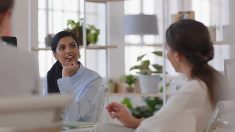business women brainstorming discussing strategy having conversation in relaxed office workspace