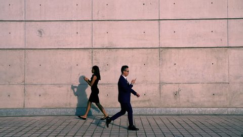Young male and female business people in formal wear walking on street looking at their smartphones ignoring each other addicted to social networks.Antisocial millennials, technology and communication