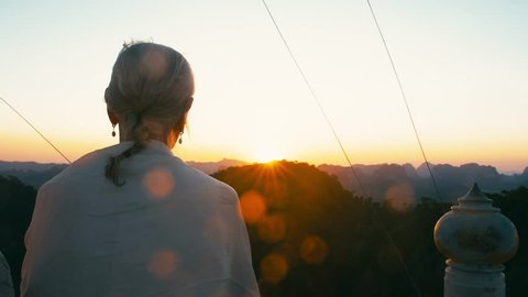 Rear view of undefinable elderly woman with gray hair waching sunset on a summer evening.