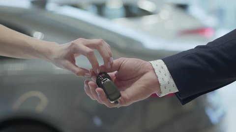 Male hand gives a car keys to famale hand in the car dealership close up. Unrecognized auto seller and a woman who bought a vehicle shake hands.