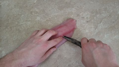 Home cooking - Checking and removing bones from Mahi-mahi fish filet placed on kitchen counter top using pliers.