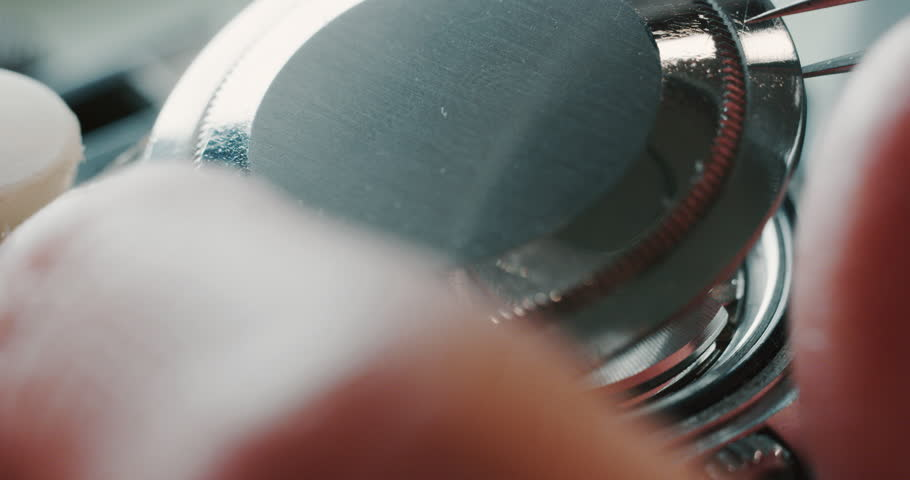 Slow motion close up of a professional watchmaker repairer working on a luxury mechanism watch gears in a workshop.
