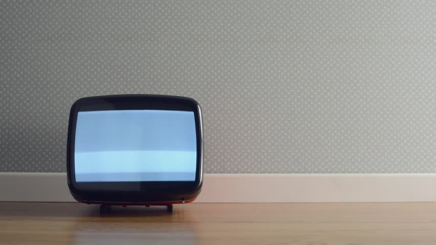 Vintage old television on the floor with static screen, a soccer ball hits it and turns it off
