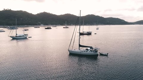 Aerial drone view of boats anchored in the bay with clear and turquoise water on the sunset. Boat and yacht in the tropical lagoon. Tropical landscape. El Nido, Palawan island, Philippines.