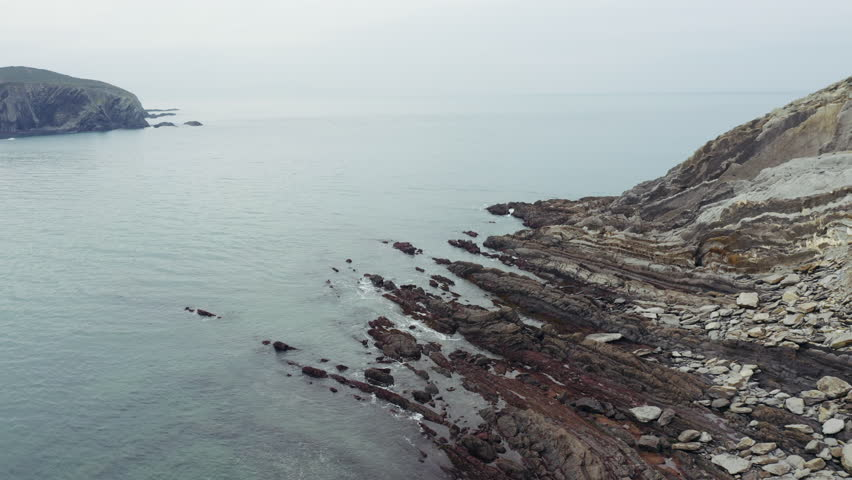 Aerial drone flight around rocky seashore; eroded by sea coast cliff, steep slope; calm turquoise water of Atlantic ocean; cloudy foggy day in Spain north; winter in Basque country; seascape panorama | Shutterstock HD Video #1025204360
