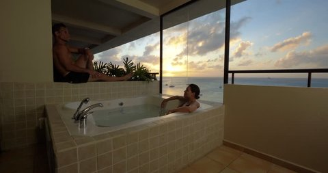 Couple in Hot Tub on Hotel Balcony, Watching Tropical Ocean Sunset