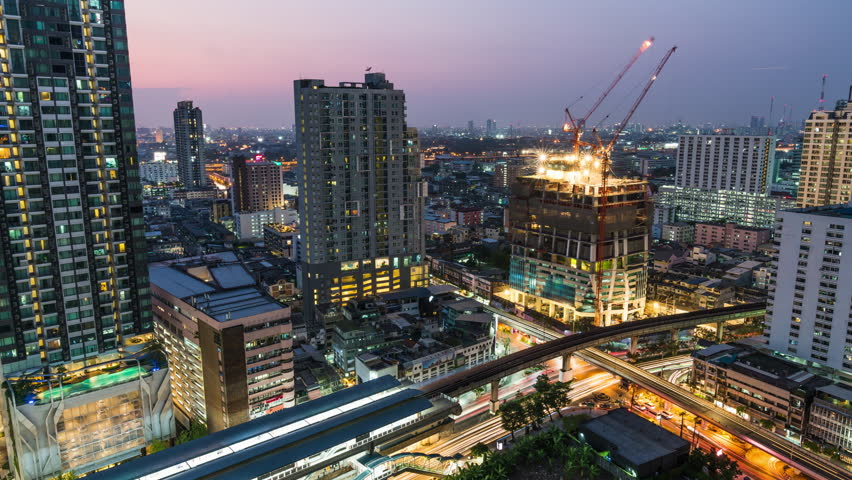 Day to night holy grail time-lapse of construction site and traffic in city. Advanced building technology, busy metro downtown cityscape, or developing industrial country concept | Shutterstock HD Video #1025238410