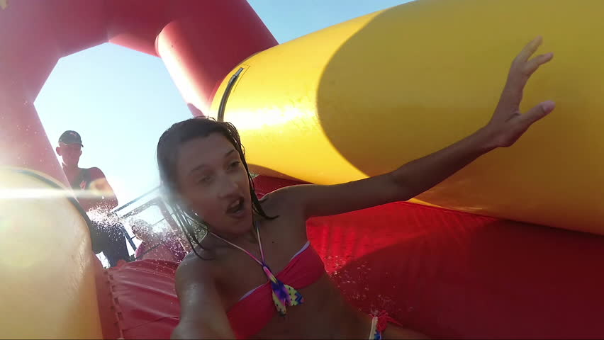 Happy cute young girl sliding down a water slide at aquapark, Summer holiday, outdoors