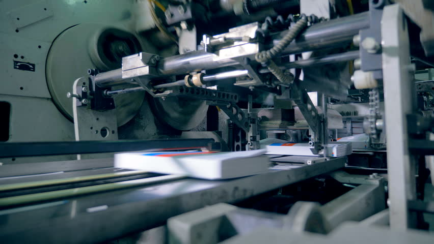 Printed books moving on a conveyor, close up. #1025305850