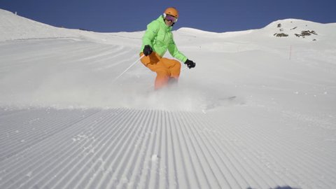 sport footage, skilled male skier skiing in short swings on freshly prepared empty ski piste on sunny winter day with clear blue sky stopping in front of camera in slow motion