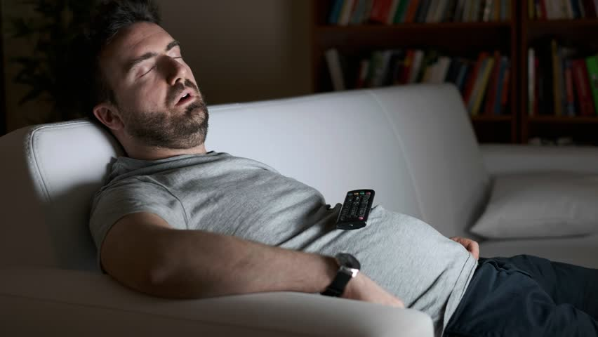 Video is about one lazy man asleep watching television at night alone | Shutterstock HD Video #1025366870