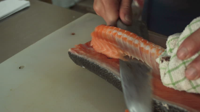 Salmon Fillets Fishbone Removal Procedure. Chef is removing salmon fishbone on cutting board for make sushi. 4k 3840x2160 high resolution footage food and drink category | Shutterstock HD Video #1025399990