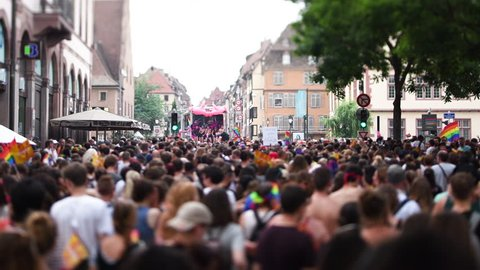 STRASBOURG, FRANCE - CIRCA 2018: Large crowd of people following gay pride truck at annual FestiGays pride gays and lesbians parade marching French streets dancing fun party atmosphere