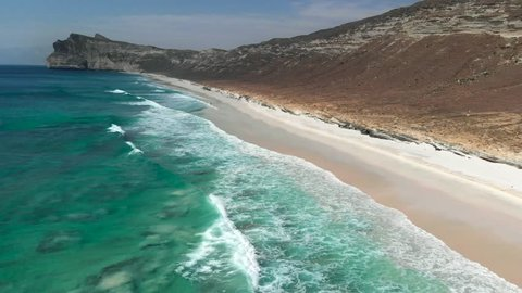 Flying over beautiful turquoise foamy waves of Indian ocean coming on a sandy beach near Salalah, Oman. Aerial shot, UHD