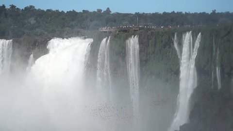 People watching a swarm of birds flying in front of powerful Iguazu Falls waterfall at the border between Brazil and Argentina.