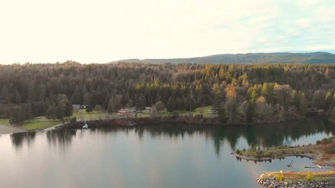 A panoramic view of a tranquil mountain lake with a small cottage beside it at sunset.