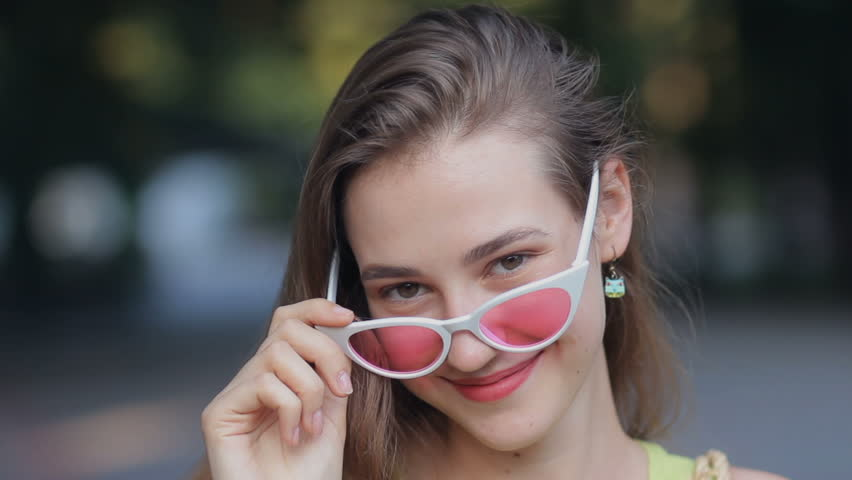 Close up portrait beautiful girl wearing pink sunglasses friendly smiling to camera street outdoors